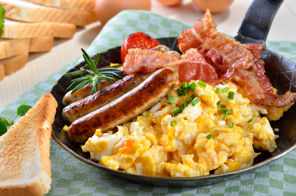 Am American breakfast with eggs, sausages and tomato with a side of toast