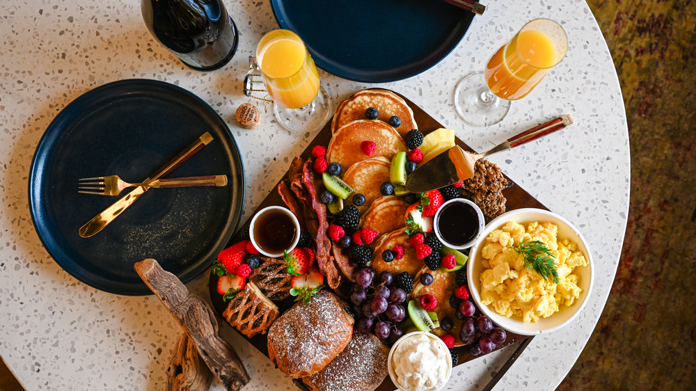 A Brunch platter with pancakes, bacon, eggs and pastries with mimosas