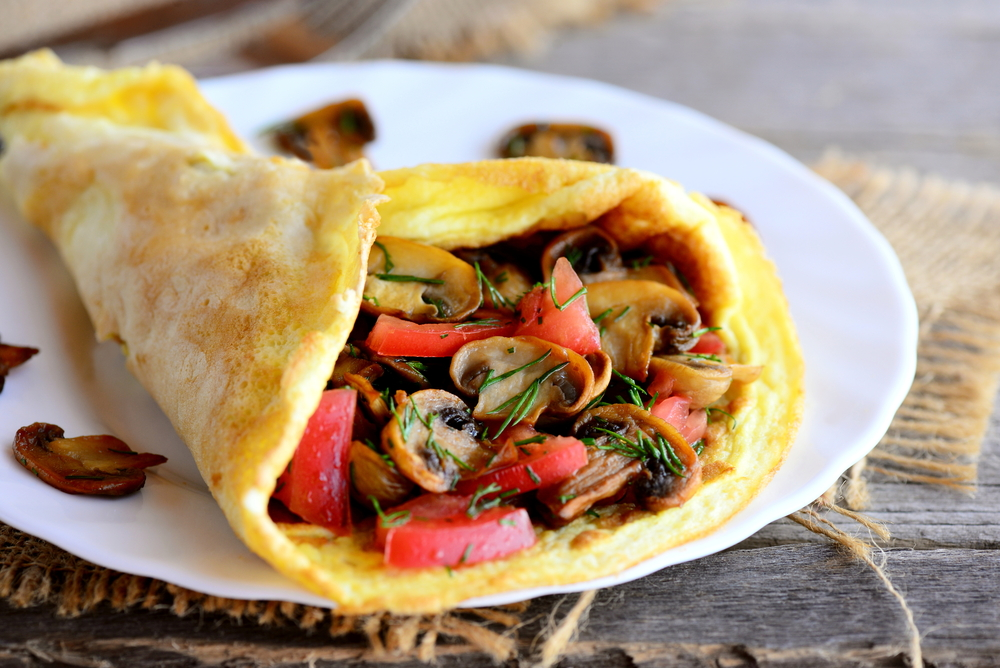 Omelet filled with mushrooms and tomatoes