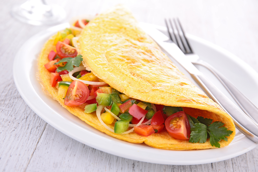 An Omelet filled with vegetables on a plate with a knife and fork in an article about breakfast in St Louis