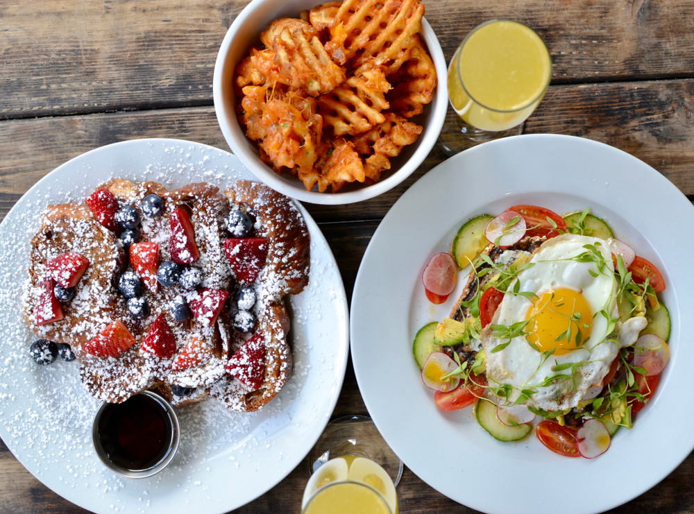 Berries on toast with egg and avocado on toast and some waffle fries