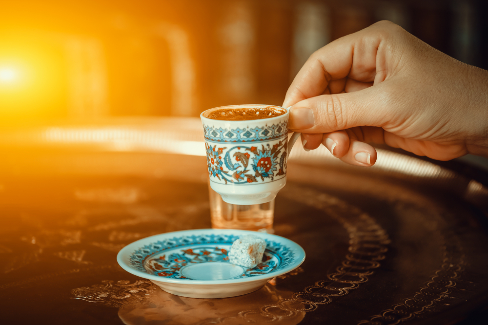 Women holding a Turkish coffee in a decorated cup in an article about breakfast in St Louis
