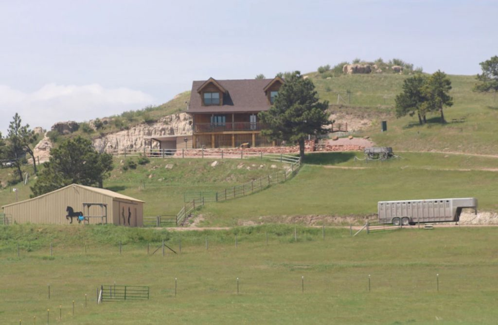 Looking at a cabin that is slightly in the distance on the side of a grassy hill. There are grassy hills all around it and some rocky cliffs.