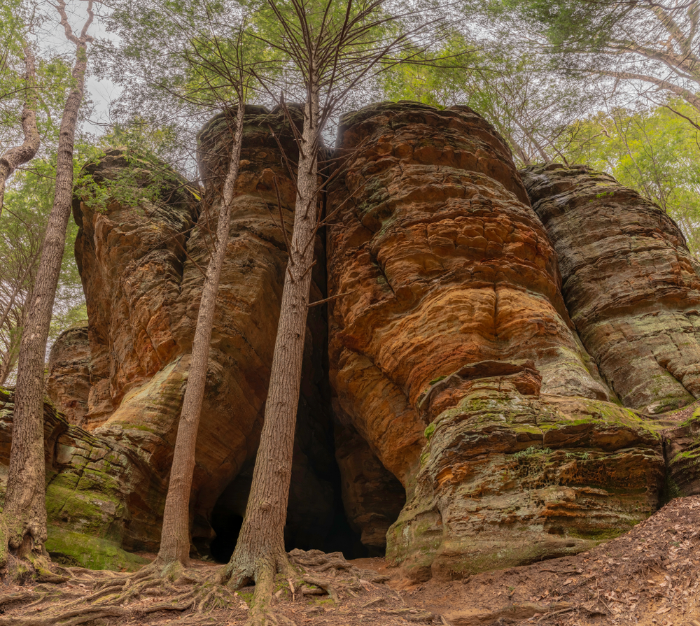 The exterior of a massive rock formation that has created an opening that looks like an old chapel. In front of it are tall trees and you can just barely see the tree canopy. The rock formation is different shades of tan, orange, and yellow, with some moss growing on it. One of the coolest hidden gems in Ohio.