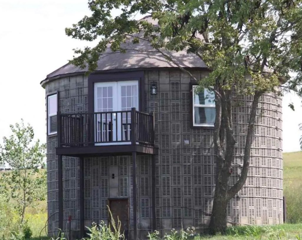 The exterior of an old corn crib that has been turned into one of the most unique cabins in Nebraska. It is gray with white windows and there are a few large trees around it as well as grass.