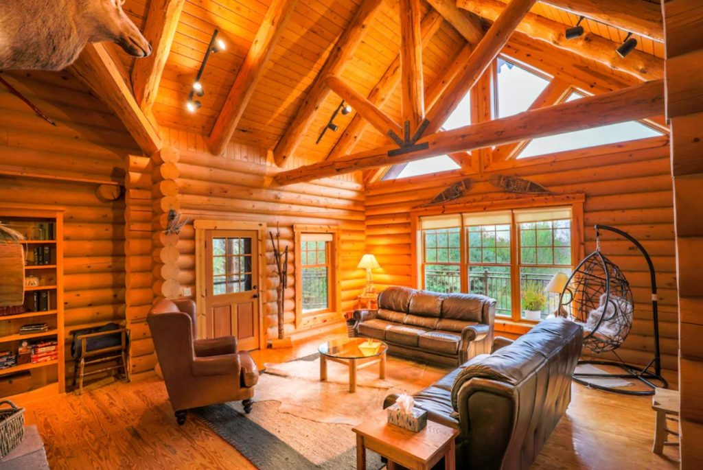The inside of a classic log cabin. There are two leather sofas, a leather chair, lots of windows, and beams across the ceiling.