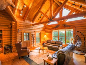 Log cabin interior with A-frame roof, large glass windows.