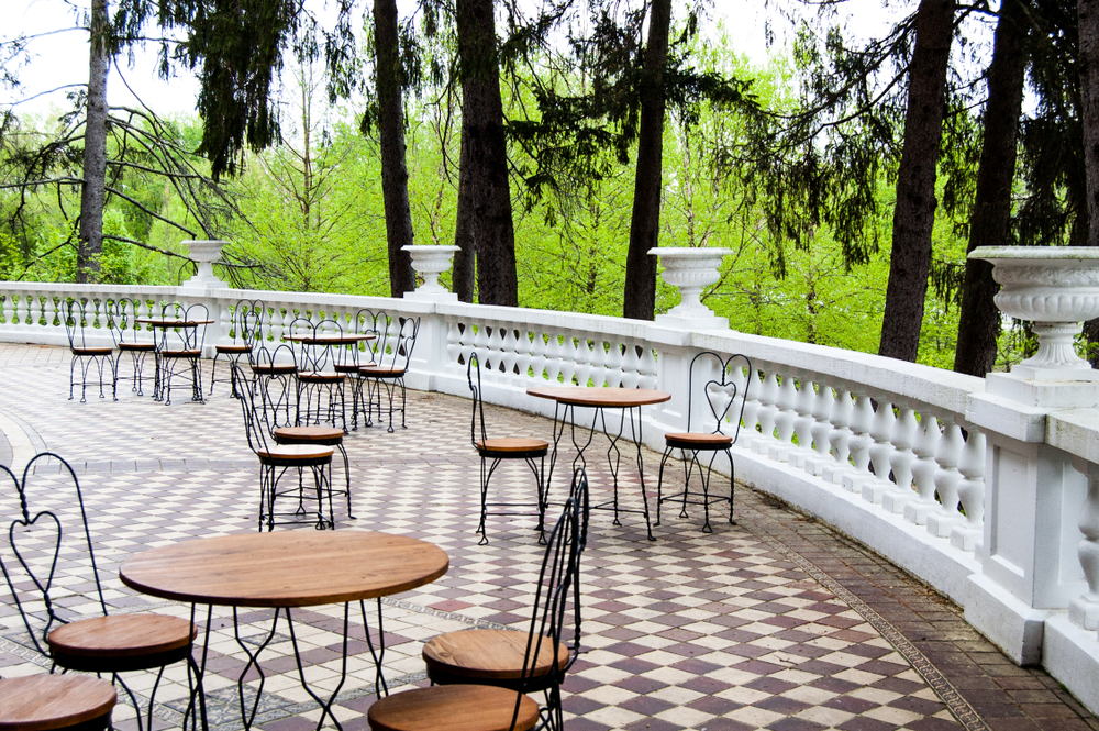 The patio of a historic home in French Lick, one of the best weekend getaways in Indiana. There are metal and wood bistro tables set up, and the patio is parquetted with a white railing with white planters on it. You can see trees past the patio.