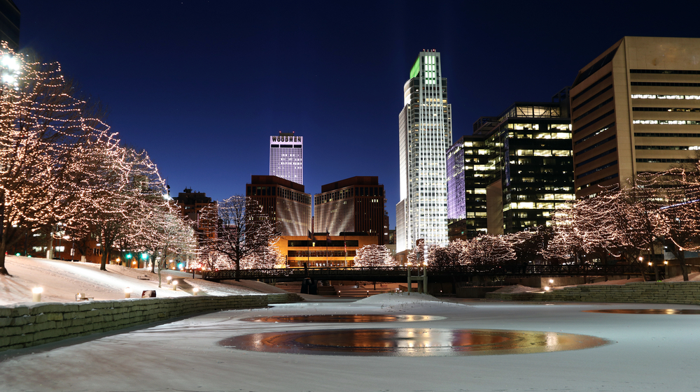 A view of the Omaha skyline from the Gene Leahy Mall, one of the fun things to do in Omaha. It is nighttime and all the buildings are lit up. There are twinkle lights in the trees and the river looks frozen over with snow on the ground.