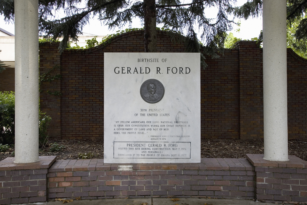 A plaque commemorating the birth site of President Gerald R. Ford. It is white marble and is sitting on a short dark brick wall with white columns. There is a metal coin with Fords face on it and the marble slab is engraved.