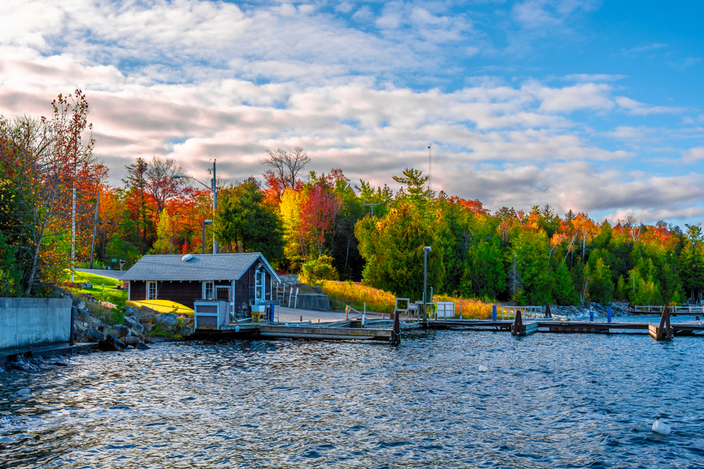 A small wooden cabin on the shores of a lake with a small dock. Behind the cabin you can see a dense forest with trees with green, yellow, orange, and red leaves. The sky is bright blue with thin clouds. One of the best Wisconsin road trips stops.