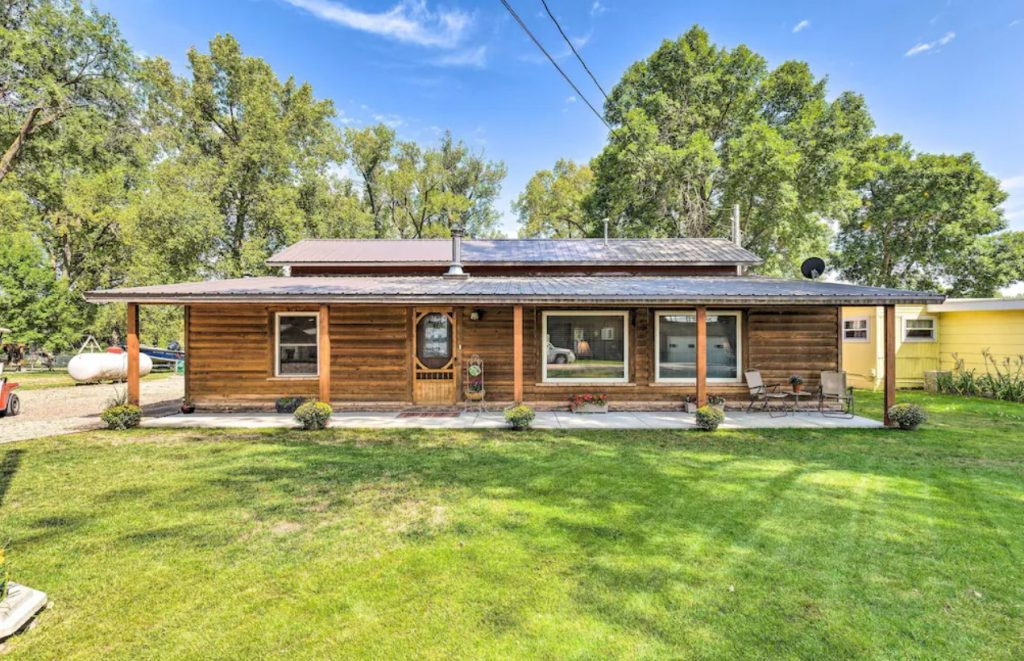 A long ranch style cabin with large windows, a covered front patio, and a large green front yard. One of the best cabins in Nebraska.