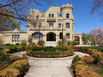 Castle museum in Omaha Nebraska made of light colored stone with turrets.