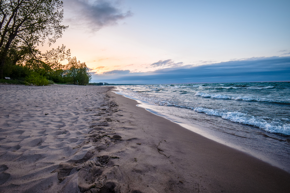 A beach on Lake Michigan. You can see small waves in the water, a sandy beach, and a small chunk of grassy area with trees. The sun is setting.