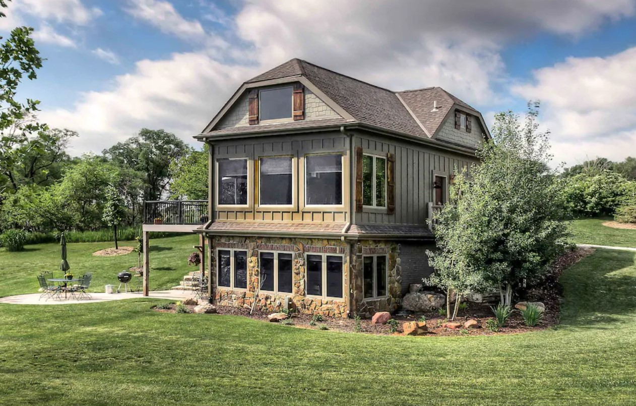 The exterior of a chateau style cabins in Nebraska. It is a light green on the top two floors and the bottom floor has stone on the front. You can see a grassy lawn, a patio, and lots of trees.
