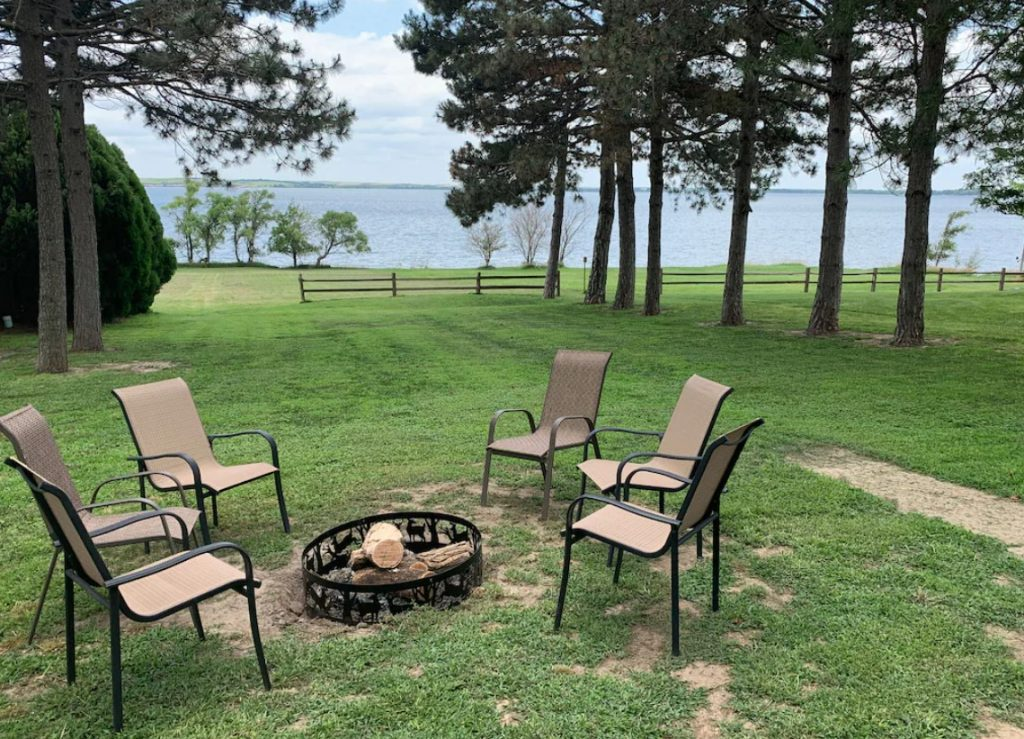 A firepit in the backyard of a cabin that looks out onto a lake. You can see the big backyard, tall trees, and the lake.