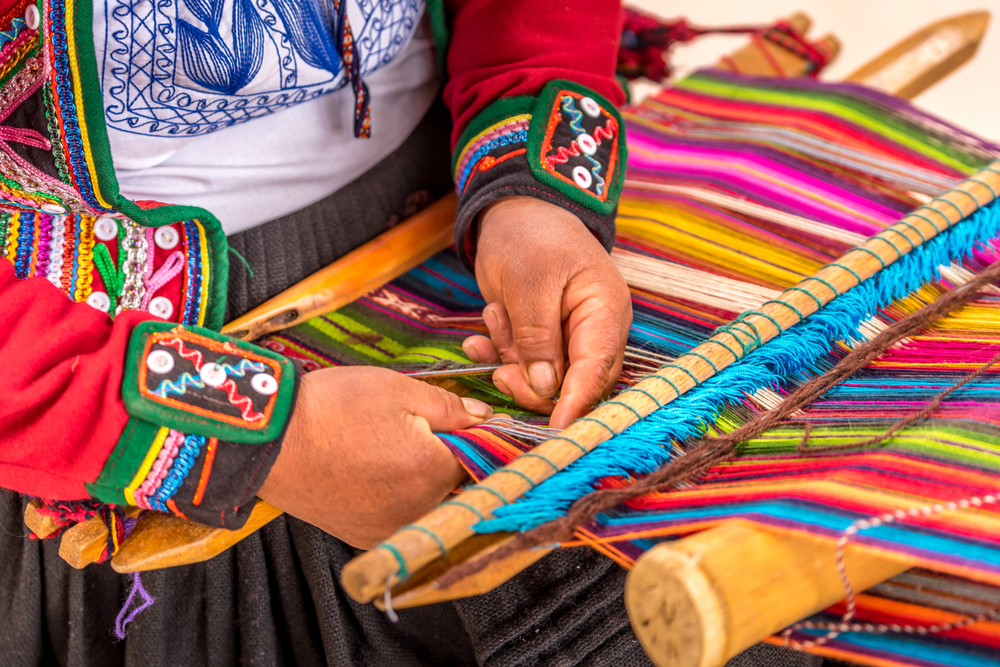 The hands of someone wearing a colorful Latin outfit while they weave using multicolored threads on a large loom.