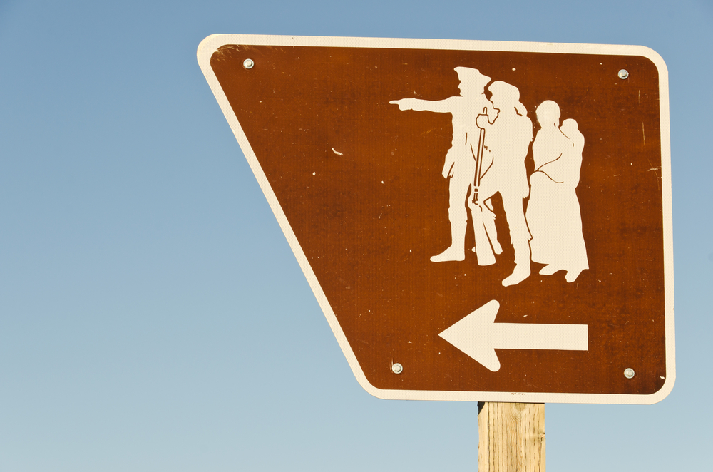 A brown sign on the side of the street. The sign has an odd shape and silhouettes of Lewis, Clark, and Sacagawea with an arrow pointing to the left.