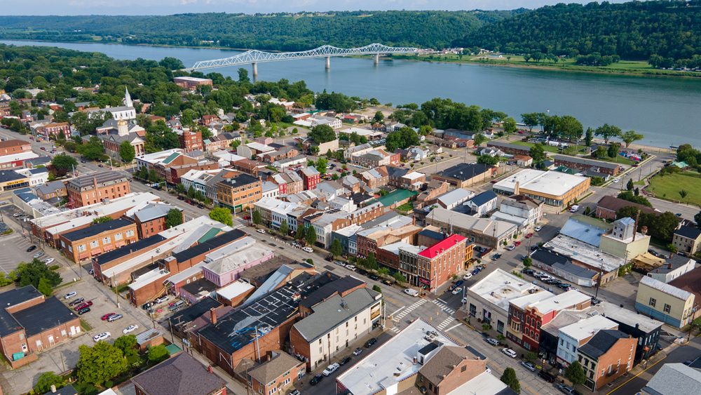 An aerial view of the small town of Madison Indiana. It is on the banks of the Ohio River. You can see old buildings on the main street, an old church, and more industrial buildings. You can also see the Ohio River and across the river to the other bank where there is green space and lots of trees. You can also see a white bridge crossing the river. Visiting Madison is a perfect weekend getaway in Indiana.