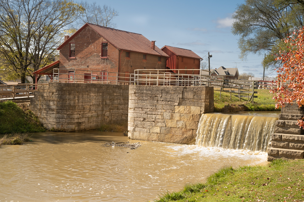 An old grist mill that leads into a river. The mill house is old brick and you can see parts of it that have been patched up. The mill is made out of old stone and creates a small waterfall that runs into a cloudy brown river.