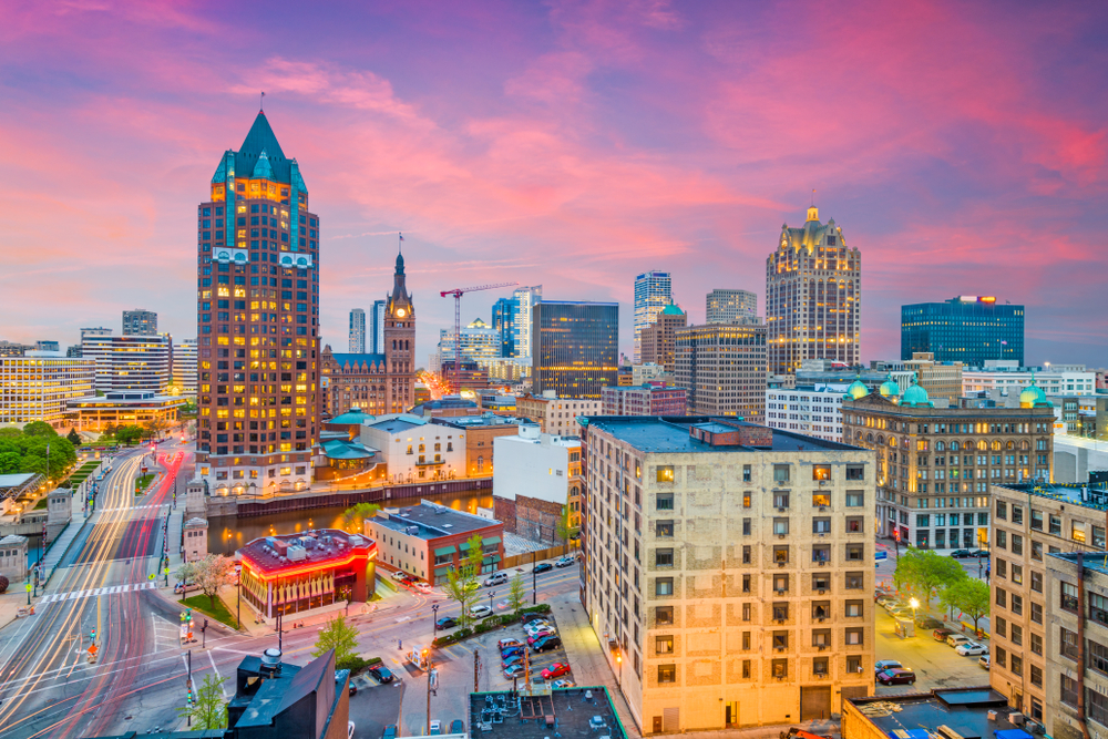 The skyline of Milwaukee at twilight, one of the best places for Wisconsin road trips. The buildings are all lit up and the sky is pink, purple, and blue.