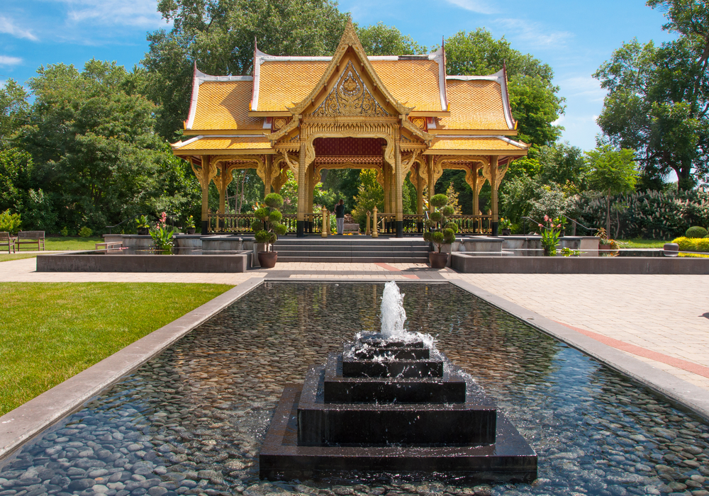 One of the coolest Wisconsin road trips destinations, a botanical garden with a golden thai-inspired pavilion, a large fountain, and a grassy area surrounded by trees.