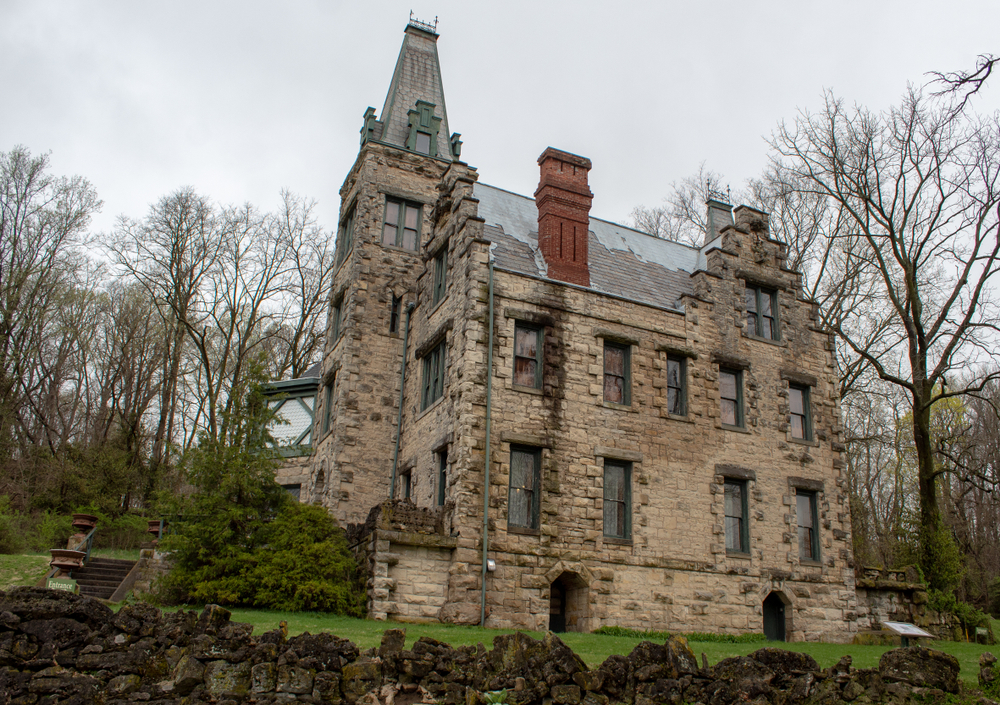 The side of a large stone castle that has Gothic architecture. All around there is a lawn with green grass, dense trees with no leaves, and a stone fence.