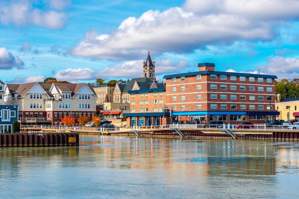 Looking at a port town that has some brick buildings, a church steeple, and a marina. The sky is very blue with big fluffy clouds. Its a great stop on Wisconsin road trips.