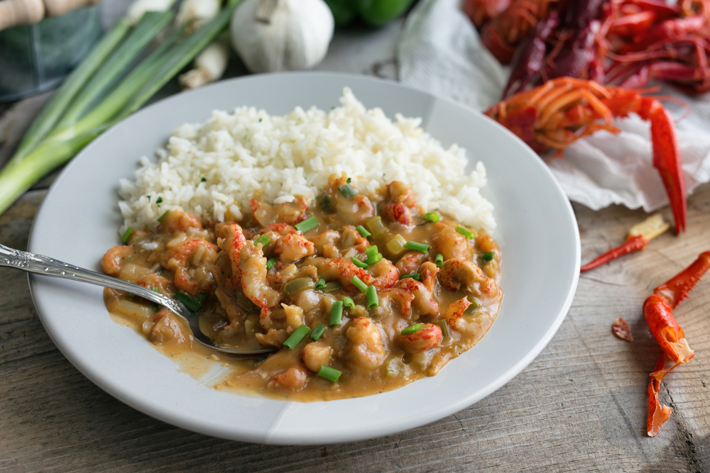 Crawfish Étouffée on a plate with rice and some crawfish shells and spring onions in the background