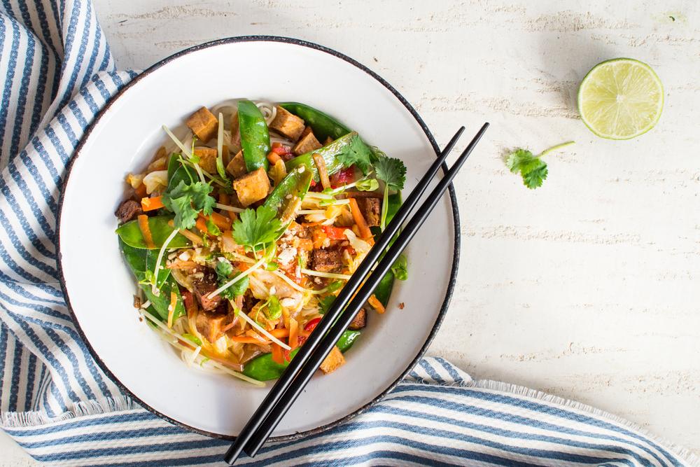 A tofu stir fry dish on a table with a blue napkin