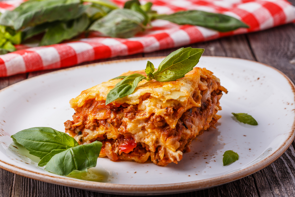 Lasagan on a plate with a red check tablecloth in the background in an article about restaurants in Indianapolis