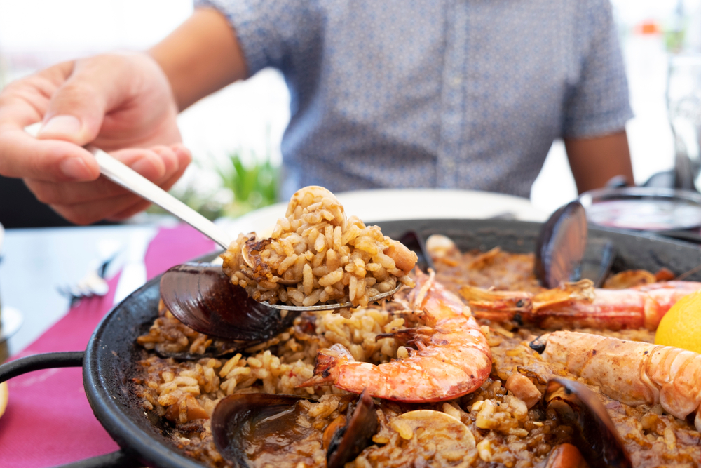 close up of a person with a spoonful o paella coming from the paella dish.