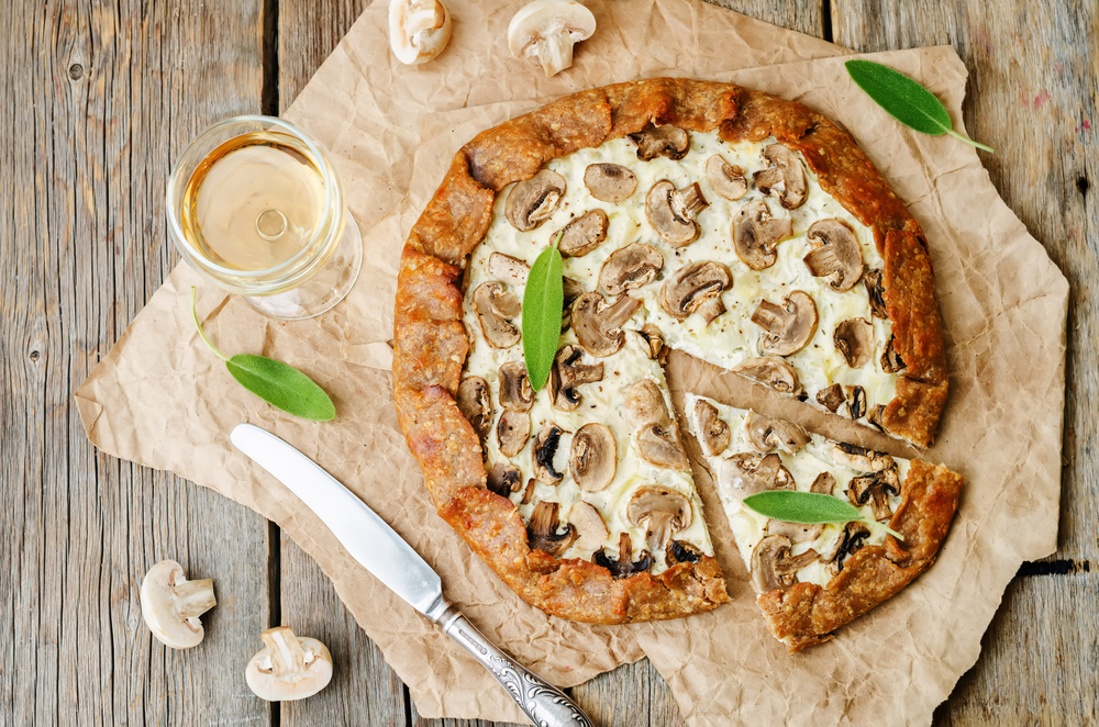 A mushrooms pizza on a table with cut mushrooms a knife and a glass of wine
