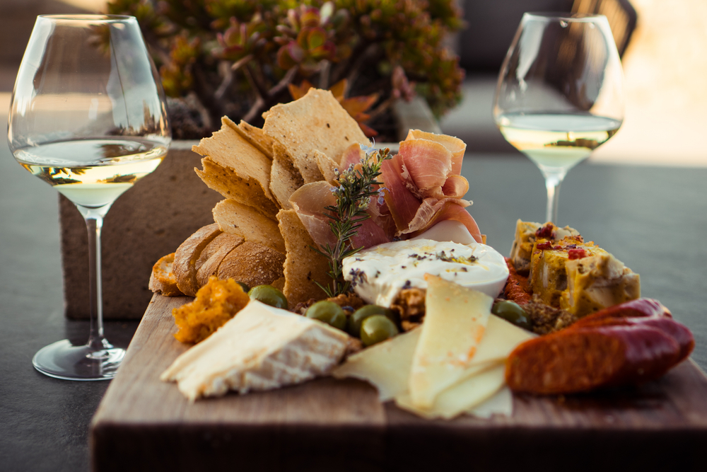 A charcuterie board with chees and ham and two glasses of white wine.