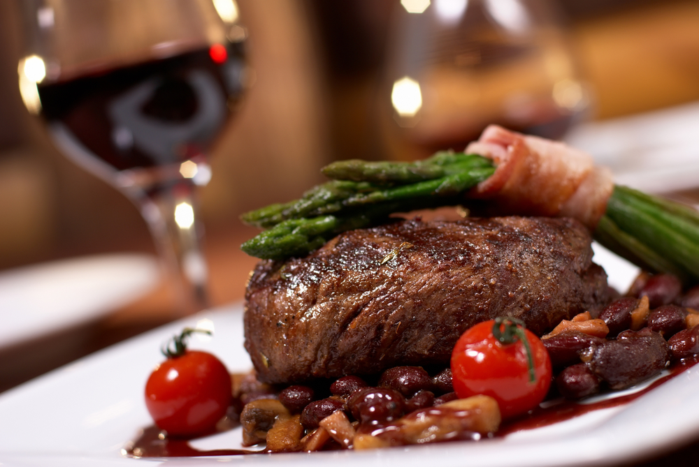 A steak on aplate with tomatoes and asparagus and a sauce