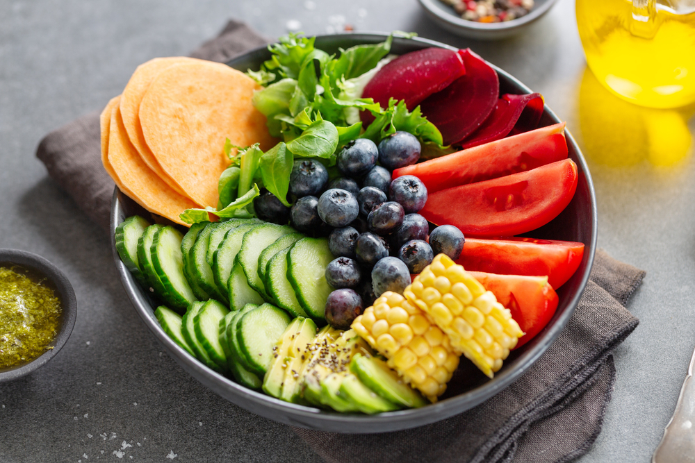 A vegan buddha bow with cucumber, blueberries, tomatoes and corn