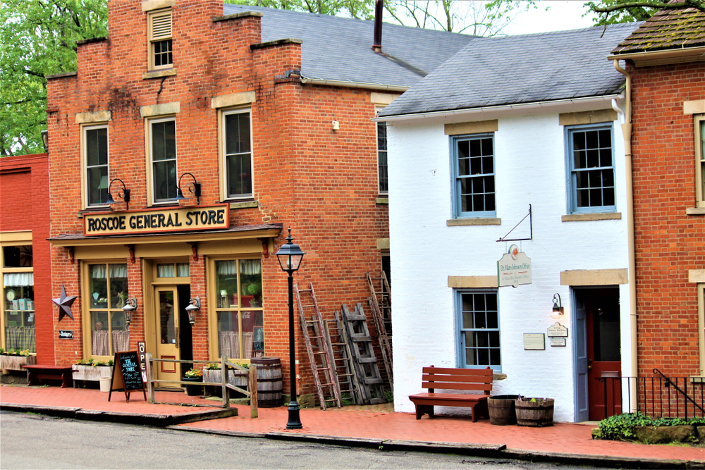 A street in a historic refurbished canal town in Ohio. The buildings are brick and one in the middle is painted white with blue trim. One of the brick buildings is a general store.