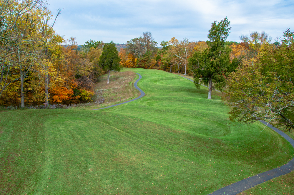 Looking slightly above an effigy mound that snakes like a serpent down a hill covered in green grass. There are pavement paths on either side of the hill. There are also trees with yellow, red, orange, and green leaves. One of the most unique hidden gems in Ohio.