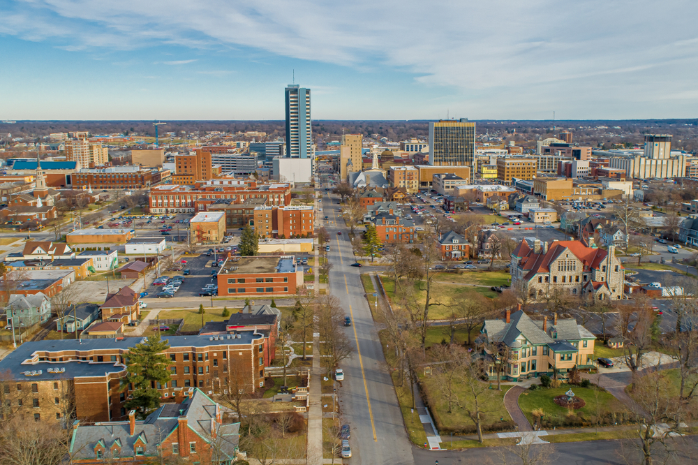 An aerial view of South Bend, one of the best weekend getaways in Indiana. You can see large old homes, churches, and buildings. There are also taller newer buildings, grassy areas, and trees with no leaves.