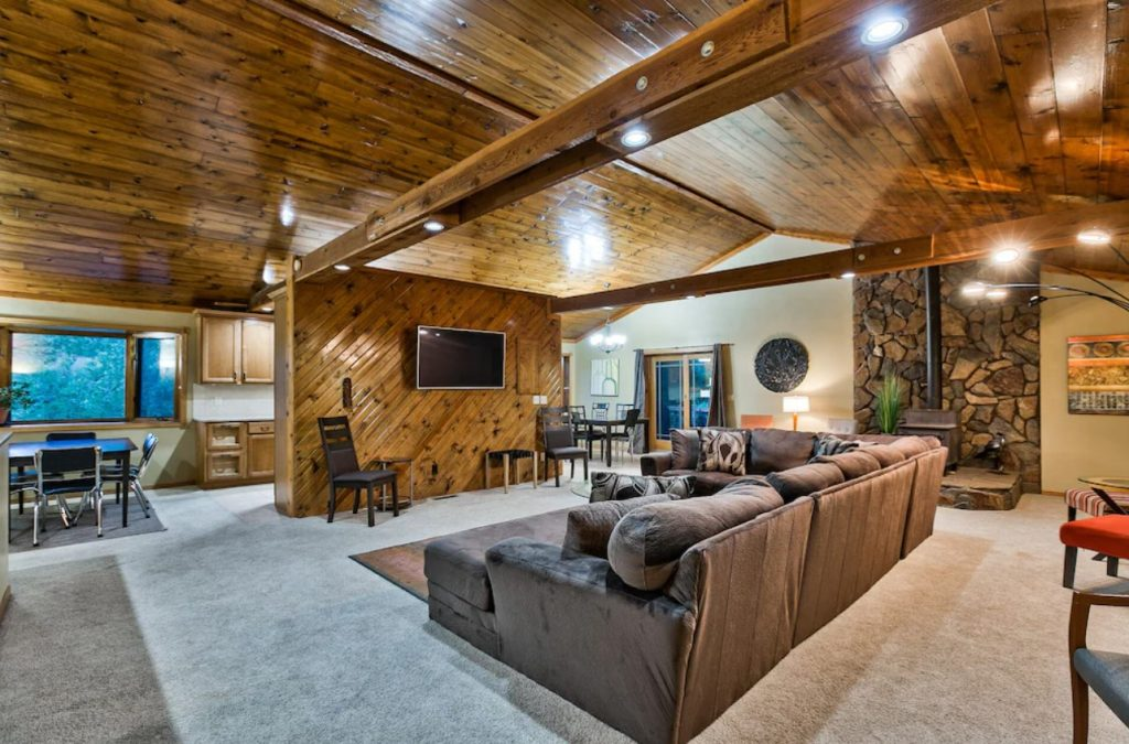 The inside of a large and spacious Nebraska cabin. There is a sectional sofa, a wall made of wood planks, a large stone hearth with a wood burning stove, lots of windows, and wood planks on the ceiling.