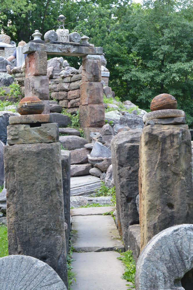 The entrance of a man made temple that's one of the most unique hidden gems in Ohio. It is made out of different sizes and types of rocks. Behind the temple you can a dense forest and there is grass growing in the cracks of rocks.