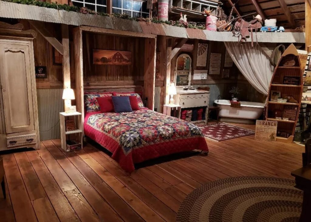 The inside of a restored barn that has a bed with a red and blue quilt, a soaking tub, and tons of different cottage and cabin themed decorations.