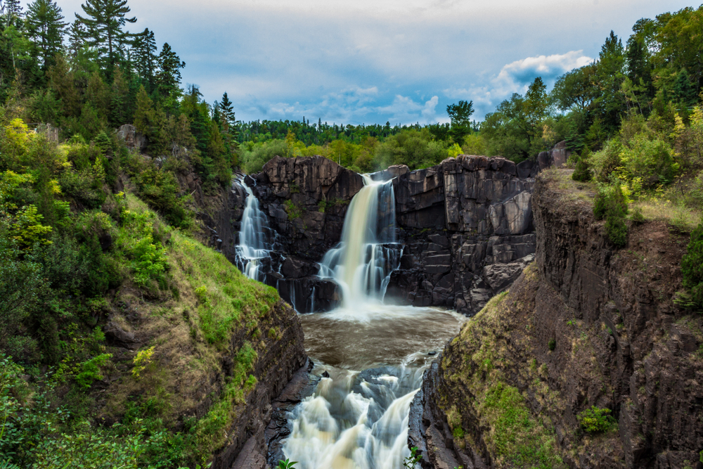 High Falls Waterfall. Rocks with water pouring over them and trees all around the top. Things to do in Grand Marais MN