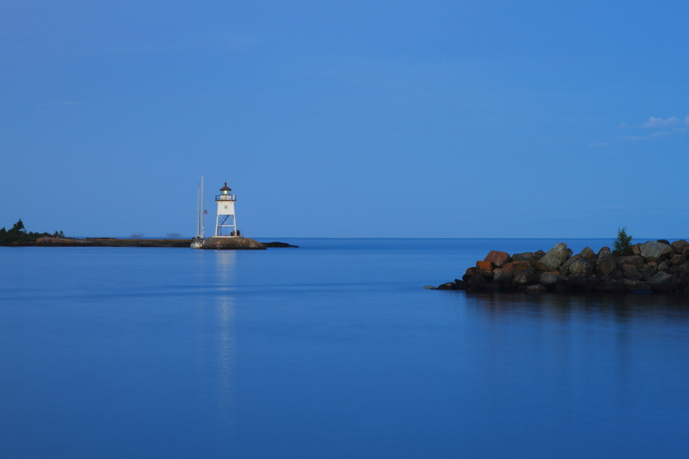 Lighthouse on an outcrop in the sea at nighttime
