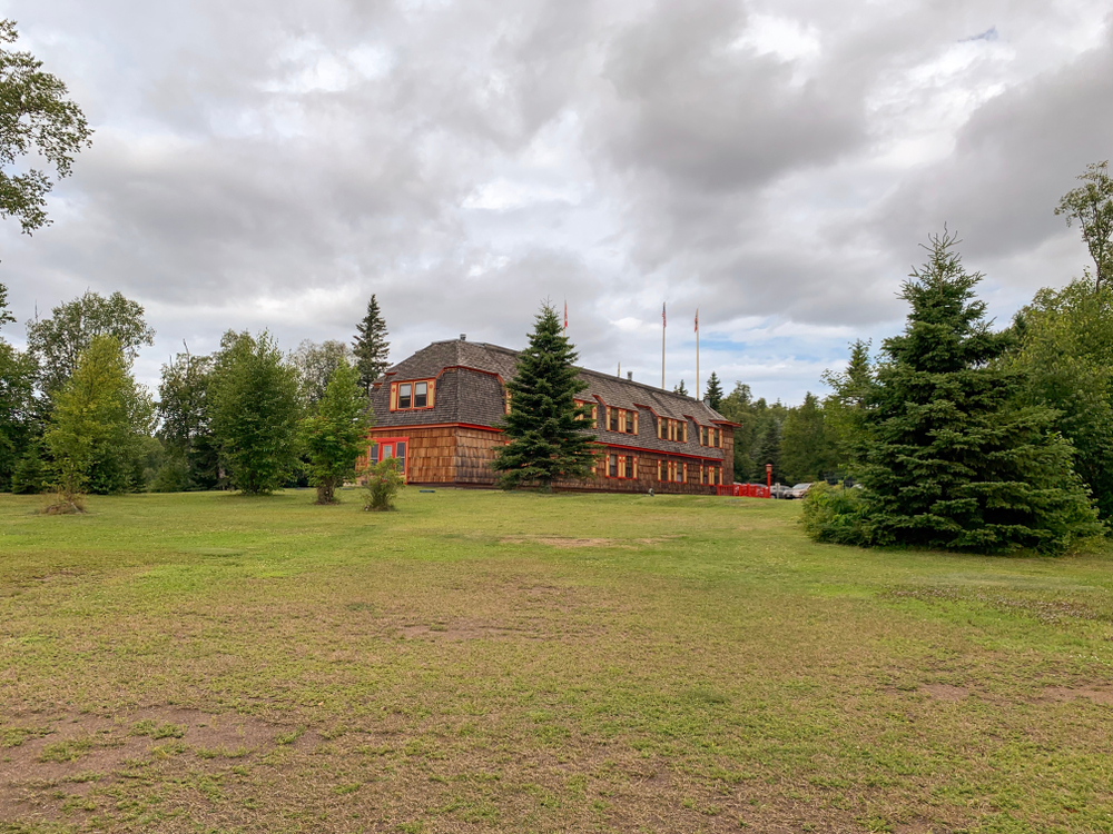 Green expanse with trees and a rustic brown wooden lodge in the background in an article about Things to Do in Grand Marais