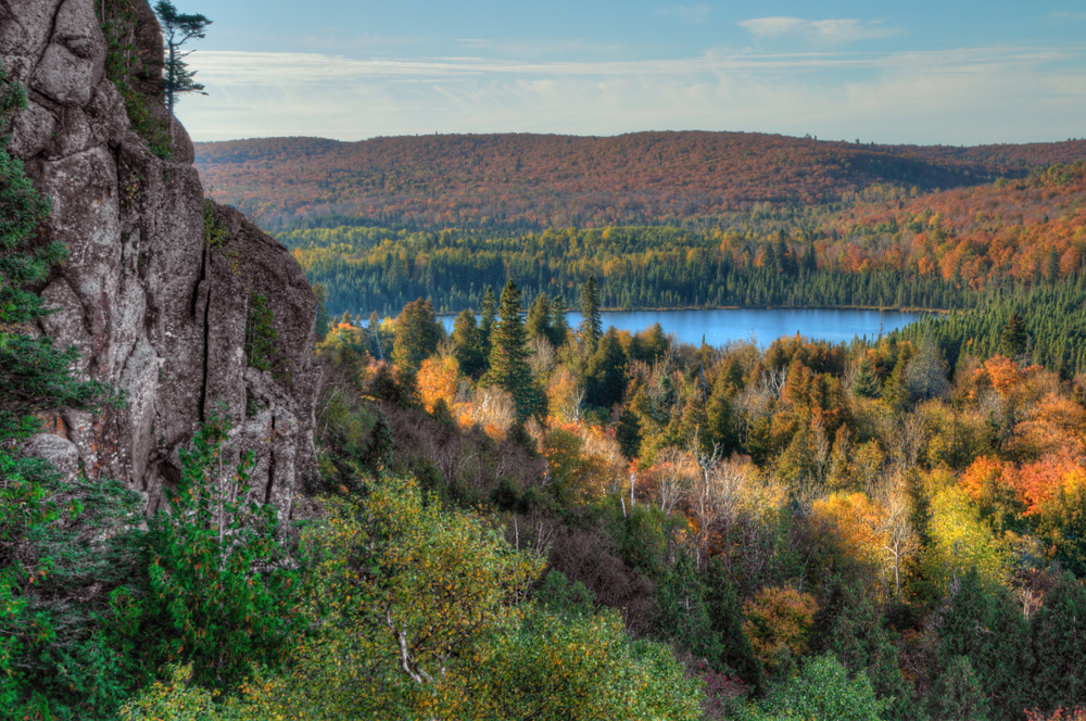 View over Oberg Mountain with a rock in the foreground, tress and fall foliage and a lake in the background.