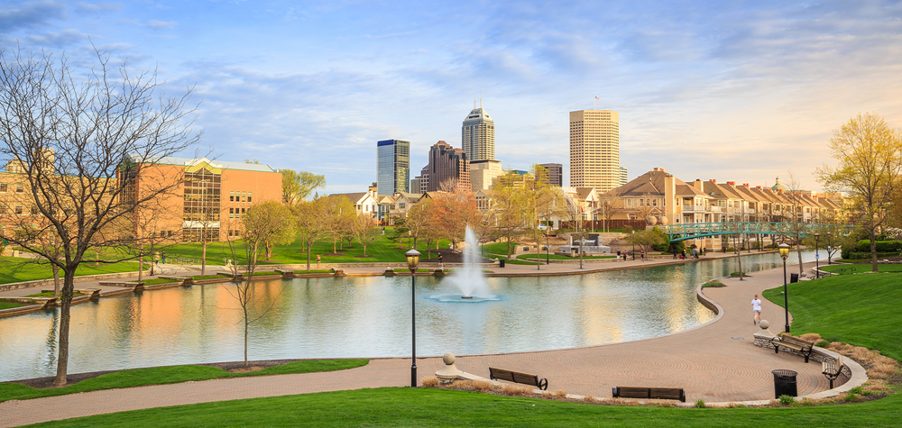The view of a canal, park, and walkway in Indianapolis, one of the best weekend getaways in Indiana. You can see the city skyline in the distance.