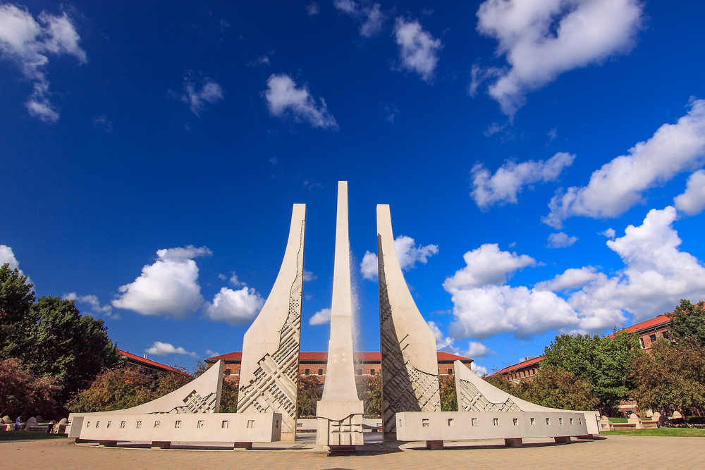 A large sculpture that is separated into three main pieces with two shorter than the one in the middle. Behind it you can see brick buildings with red roofs and a bright blue sky with fluffy clouds.