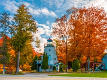 White lighthouse surrounded by autumnal colored trees. co