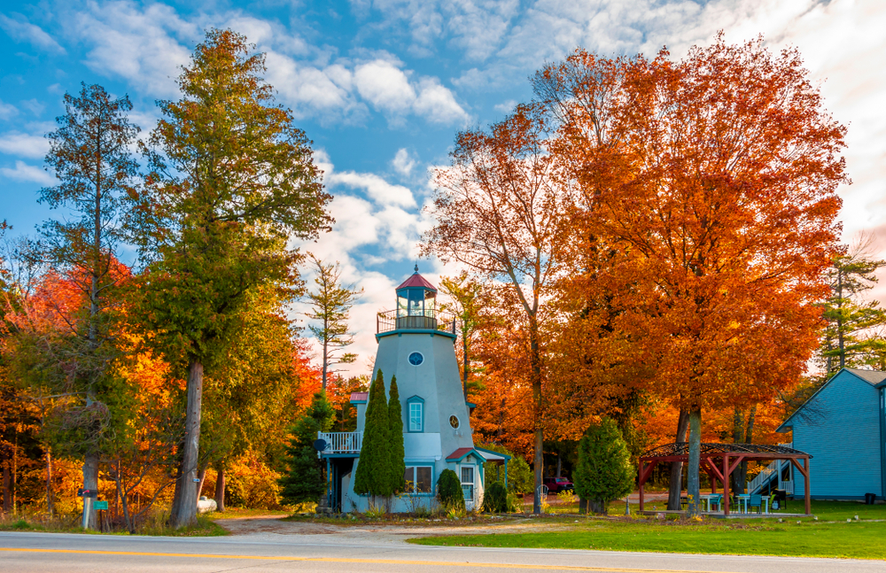 A small lighthouse in a grassy area surrounded by trees with orange, red, yellow, and green leaves. The lighthouse is light gray with a red roof. One of the best Wisconsin road trips stops.